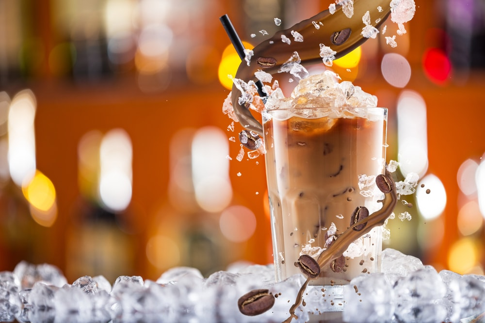 Cold coffee drink with ice, beans and splash close-up