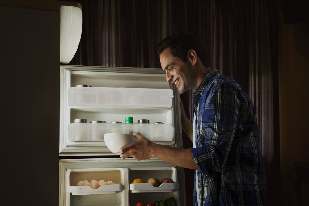 Young man standing in the kitchen searching food in the fridge at night