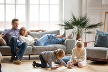 Children sister and brother playing drawing together on floor while young parents relaxing at home on sofa