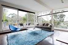 Glassed wall Australian living room with amazing views of bush treetops